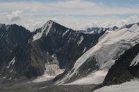 С ледника Егорова на горизонте в облаках за Алайским хребтом виден пик Ленина.